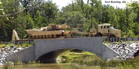 Military machinery crosses bridge on Fort Benning
