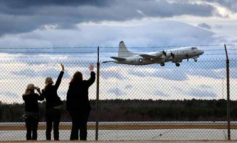 Women nod, wave after plane in Naval Air Station Brunswick